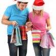 Young couple in Santa hats shopping and holding many shopping bags isolated on white — Stock Photo #18427685