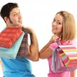 Young couple shopping and holding many shopping bags isolated on white — Stock Photo