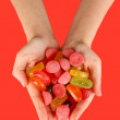 Hands full of sweets on red background — Stock Photo #18427857