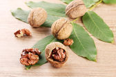 Walnuts with green leaves, on wooden background — Stock Photo