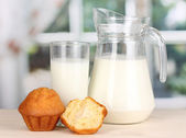 Pitcher and glass of milk with muffins on wooden table on window background — Stock Photo