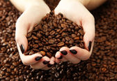 Cerrar las manos femeninas con granos de café — Foto de Stock