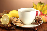 Cup of hot tea and autumn leaves, on brown background — Stock Photo