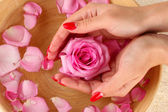 Woman hands with wooden bowl of water with petals — Stock Photo