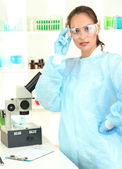 Giovane scienziato esaminando al microscopio in laboratorio — Foto Stock