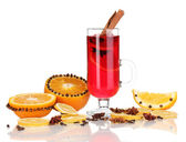 Fragrant mulled wine in glass with spices and oranges around isolated on white — Stock Photo