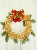 Christmas wreath of dried lemons with fir tree and balls, on wooden background — Stockfoto