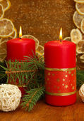 Two candles and christmas decorations, on golden background — Stok fotoğraf