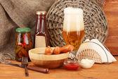 Pivo a grilované klobásy na dřevěný stůl na pozadí pytloviny — Stock fotografie