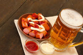 Pivo a grilované klobásy na dřevěné pozadí — Stock fotografie