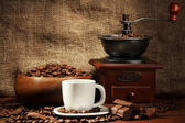 Coffee grinder and cup of coffee on burlap background — Stock Photo