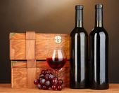 Wooden cases with wine bottles on wooden table on brown background — Stock Photo