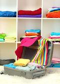 Open zilveren koffer met kleding op kamer — Stockfoto
