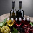 Bottles and glasses of wine and grapes on grey background — Stock Photo #18570809