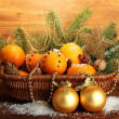 Christmas composition in basket with oranges and fir tree, on wooden background — Stock Photo #18570985