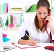 Young pretty business woman with phone writing at office — Stock Photo