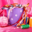 Color bucket with multicolor ribbons and thread on color fabric background — 图库照片