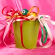 Color bucket with multicolor ribbons and thread on pink fabric background — Stockfoto