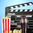 Movie clapperboard, cola and popcorn on blue background — Stock fotografie