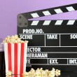 Movie clapperboard, cola and popcorn on purple background — Stock fotografie