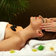 Portrait of beautiful woman with spa stones taking head massage — Stock Photo