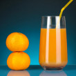 Delicious tangerine juice in glass and mandarins next to it on dark blue background — Stock Photo