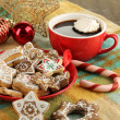 Christmas treats on plate and cup of coffe on plaid close-up — Stock Photo #18575801