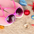 Christmas balls,seashells andh beach accessories on sand, close-up — Stockfoto
