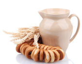 Jar of milk, tasty bagels and spikelets, isolated on white — Stock Photo