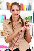 Jeune jolie femme d'affaires avec téléphone au bureau — Photo