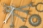 Metal cogwheels and spanners on wooden background — Stock Photo