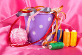 Color bucket with multicolor ribbons and thread on color fabric background — Stock Photo