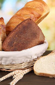 Fresh bread in basket on wooden table on natural background close-up — Stock Photo