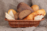 Fresh bread in basket on wooden table on sacking background — Stock Photo