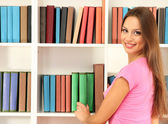 Female student selecting book from library shelf — Stock Photo