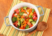 Vegetable stew in gray pot on color napkin on wooden background — Stock Photo