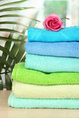 Stack of towels with fragrant flower on window background — Stock Photo