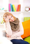 Sick woman with cold sitting on sofa — Stock Photo