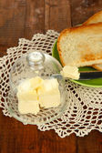 Masło na szkło talerzyk z szklaną pokrywę i świeży chleb, na tle drewniane — Zdjęcie stockowe