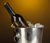 Bottle of wine in ice bucket on darck yellow background — Stock Photo