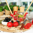 Fresh greek salad in glass bowl surrounded by ingredients for cooking on wooden table on window background — Stock Photo