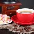 Red cup of coffee with rahat delight and coffee mill on wooden table — Stock Photo