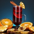 Fragrant mulled wine in glass with spices and oranges around on blue background - Stock Photo
