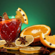 Fragrant mulled wine in glass with spices and oranges around on green background — Stockfoto