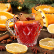Fragrant mulled wine in glass with spices and oranges around on wooden table — 图库照片