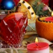 Fragrant mulled wine in glass with spices and oranges around on wooden table on red background — Stock fotografie