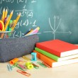 Back to school - blackboard with pencil-box and school equipment on table — Stok fotoğraf