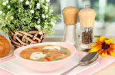 Fragrant soup in pink plate on table on window background close-up — Stock Photo
