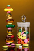 Capsules and pills hill and in receptacle on yellow background — Stock Photo