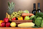Composition with vegetables and fruits in wicker basket on brown background — Stock Photo